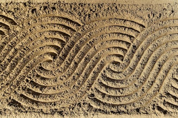 모래 배경에 연속 곡선 웨이브 패턴 아트.
