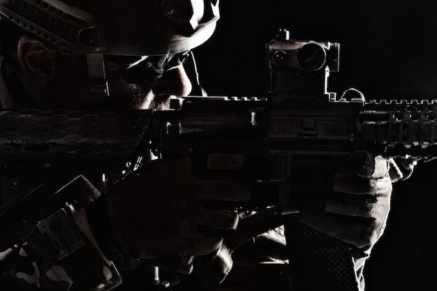 武器を指す制服を着た特殊部隊の兵士の輪郭のバックライトの肖像画、黒のクローズアップの肖像画