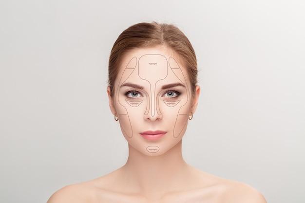 Контурная. составьте лицо женщины на сером фоне. контур и мелирование макияжа. образец профессионального макияжа лица