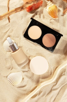 Contouring powder, foundation liquid cream and cotton sponges on golden sand with shells