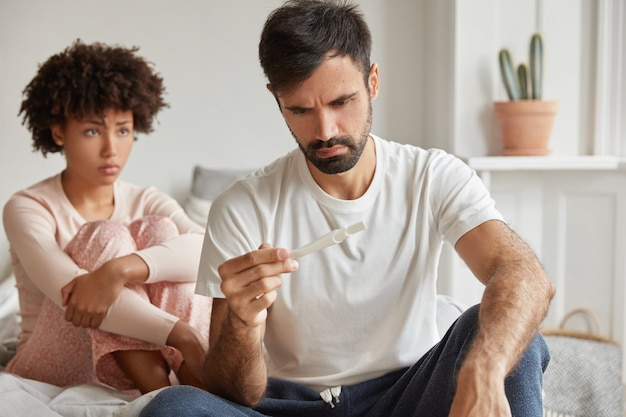 避妊は失敗し、望まない妊娠の概念。欲求不満の若い家族のカップルは妊娠検査をチェックします