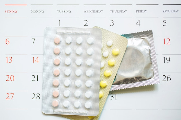Contraceptive control pills and condom on date of calendar calculate date control the birth rate. table wood. health care and medicine, contraception concept. empty space for text.
