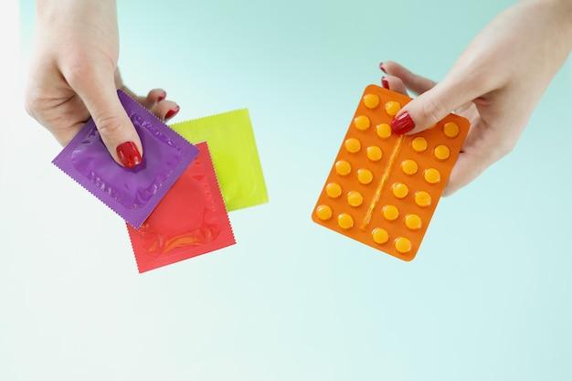 여성의 손에 있는 피임약과 피임약 임신 보호 개념 선택