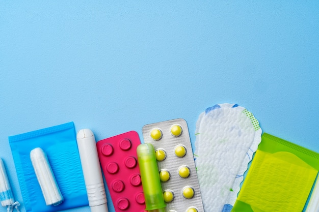 Contraceptive pills, hygienic pads and tampons on blue top view