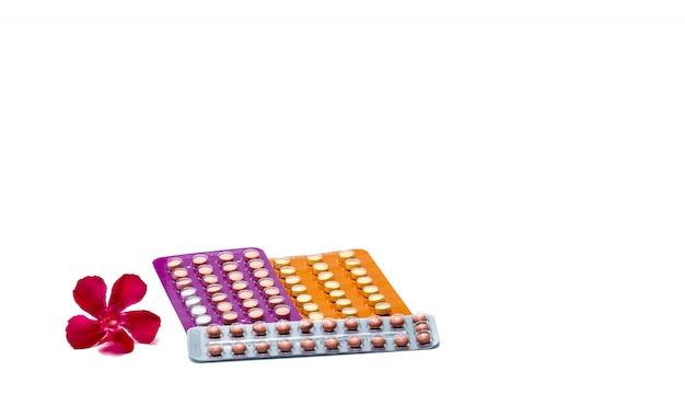 피임 환 약 또는 흰색 배경에 고립 된 핑크 꽃과 피임약. 피임 호르몬. 가족 계획 개념. 물집 포장에 둥근 호르몬 정제. 호르몬 여드름.