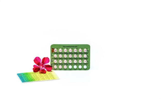 피임 환 약 또는 흰색 배경에 고립 된 핑크 꽃과 피임약. 피임 호르몬. 가족 계획. 물집 팩에있는 호르몬 정제. 여드름 호르몬 치료. 알약 팩