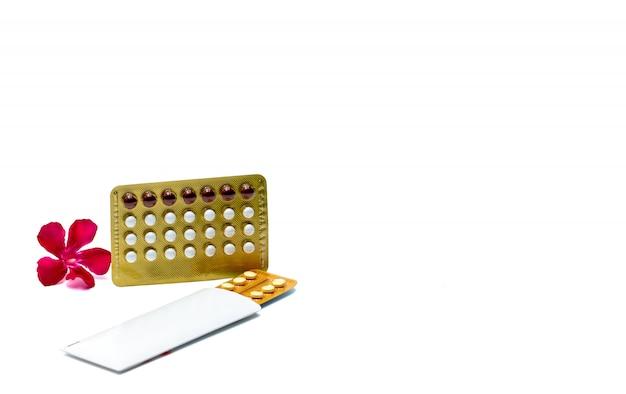 피임 환 약 또는 피임약 흰색 배경 복사 공간에 분홍색 꽃과 알 약. 피임 호르몬. 가족 계획 개념. 물집 팩에있는 백색과 빨강 둥근 호르몬 정제