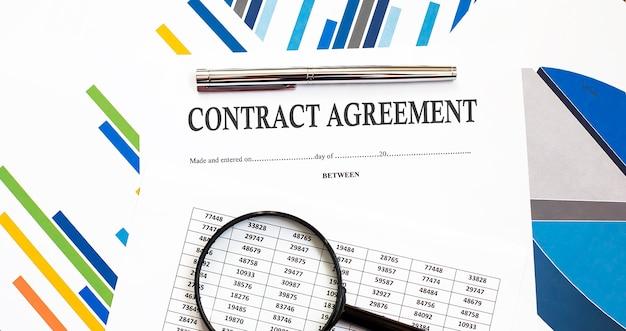 ペンと拡大鏡を使用したチャート表面の契約書