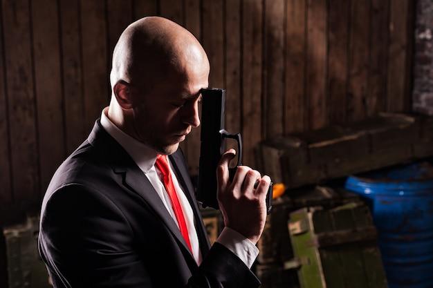 スーツと赤いネクタイの契約暗殺者は銃を保持しています。