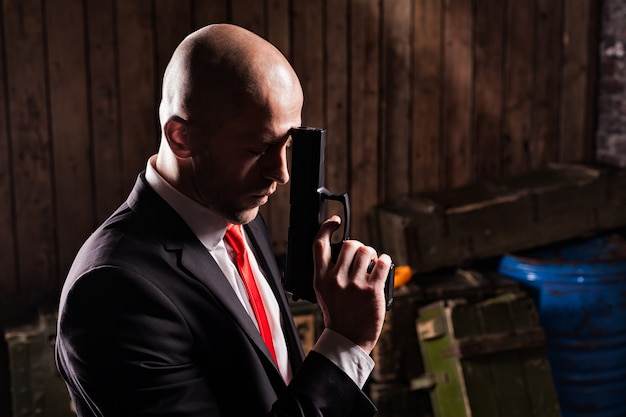 Contract assassin in suit and red tie holds gun.