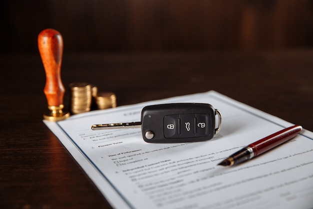 Contract for car purchase, stamp, pen and car key on a table.