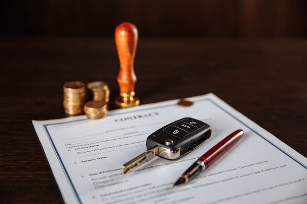 Contract for car purchase, stamp, pen and car key on wooden table.