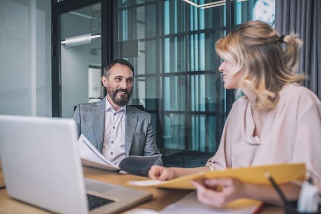 契約書、書類。オフィスのテーブルで一緒に座って書類を勉強しているビジネスカジュアルな服を着た大人のひげを生やした男性とブロンドの女性の笑顔