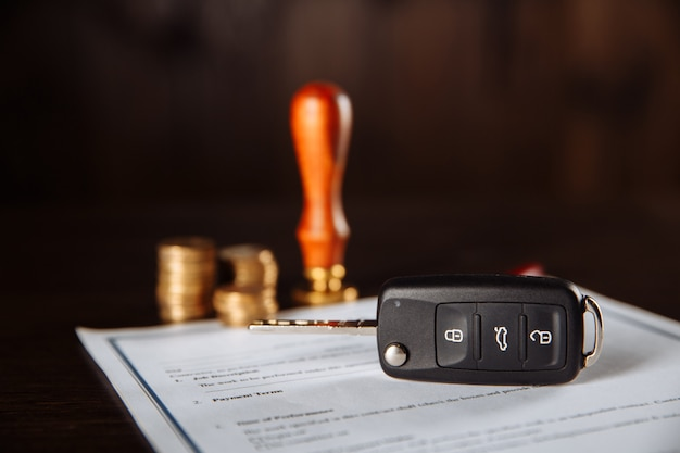 Contract form for car loan, stamp, pen and car key on wooden table.