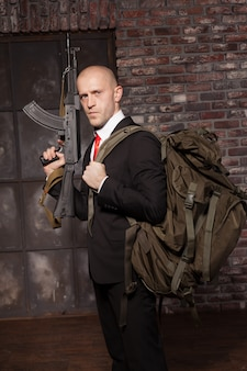 Contract killer ready for secret mission. hired murderer in suit and red tie with backpack holding machine gun in hand.