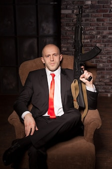 Contract killer in suit and red tie sitting in a chair and holds automatic weapon