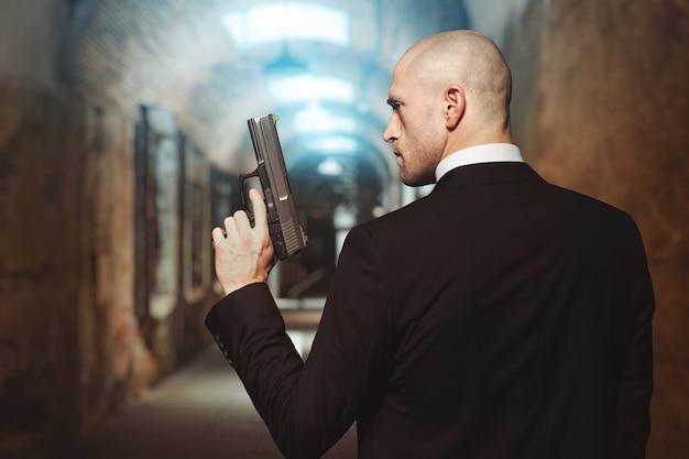 銃の壁紙のコンセプト、背面図付きの契約キラー。スーツを着たハゲの暗殺者はピストルを手に持っています。