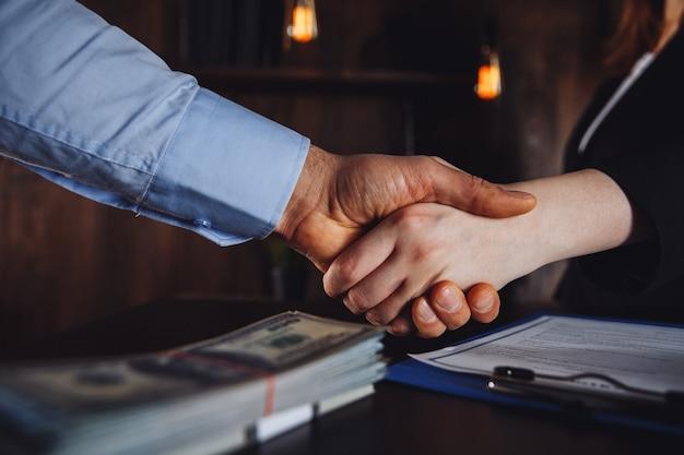 契約サインの概念。男性と女性が合意し、お金を取ります。