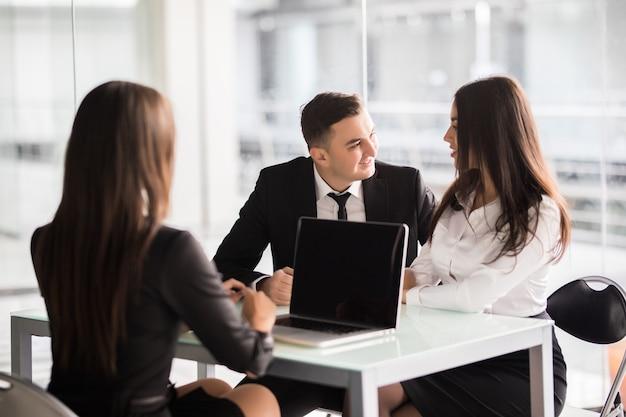 最良の条件で契約します。自信を持って若い女性がオフィスの机で若いカップルと一緒に座っている間、ドキュメントのいくつかの詳細を説明し、笑顔でそれを指しています