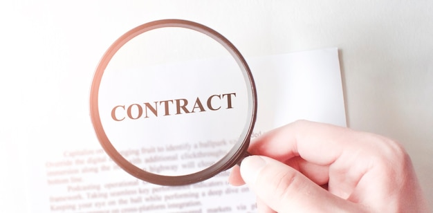 Contract with pen and magnifying glass. business concept