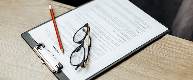A contract on a wooden work table with glasses and a red pencil. the documents are ready for signing. business concept. collaboration agreement.