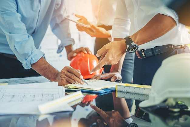 청사진을 가진 계약자 및 엔지니어는 현대 건설 현장에서 토론합니다. 기계 공장의 엔지니어는 지침을 읽습니다.