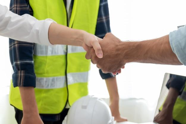 Подрядчик. рукопожатие партнера группы архитекторов и инженеров-строителей в офисе конференц-зала на строительной площадке, промышленное строительство, партнерство, контракт на строительство, концепция подрядчика