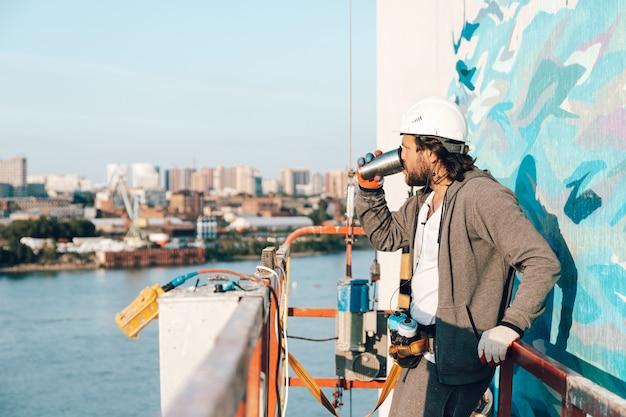 請負業者、建物のゆりかごの高地にいるアーティストが仕事を休んで、サーモカップからコーヒーを飲む Premium写真