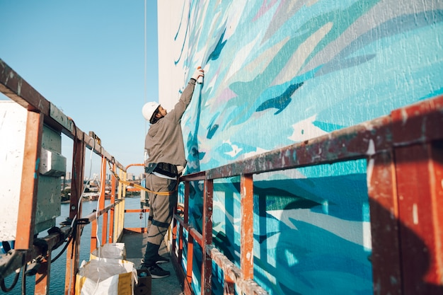 Contractor, artist at high altitude in a building cradle performs facade painting, decorating and home renovation