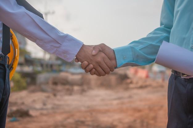 Партнерские отношения пожимают друг другу руки на строительной площадке