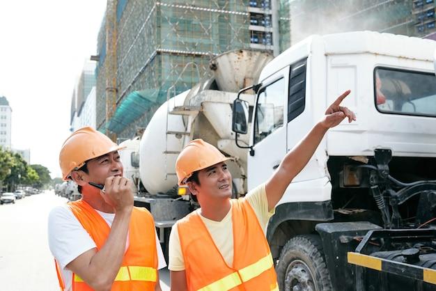 彼の同僚がトランシーバーについて話しているときに建設中の建物を指している請負業者