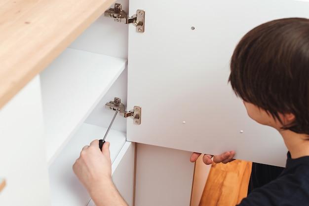 現代のアパートで新しい家具を組み立てる請負業者の修理工
