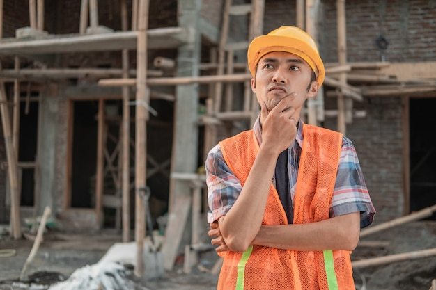 Contractor stands wearing a safety helmet and vest in the background of the unfinished building