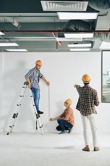 계약자는 측정 테이프로 벽에 직선을 측정하는 작업자를 통제하기 위해 자리를 비 웠습니다.
