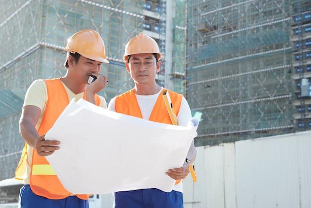 워키토키를 통해 건축업자와 대화하는 계약자