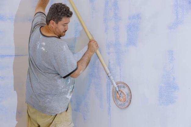 Подрядчик шлифует гипсокартон на стене с помощью песчаного шпателя.