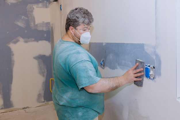 壁の乾式壁を研磨する砂こてを使用する請負業者