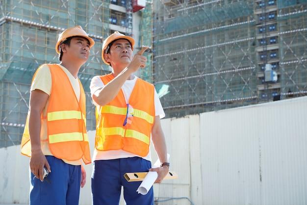 建設現場で会う際に高層ビルの外壁仕上げについて話し合う請負業者