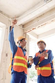 朝のコーヒーを飲み、建設中の家の天井スラブと配線について話し合う請負業者