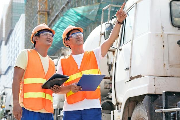明るいオレンジ色のベストの請負業者は、建設現場に立って話し合っているヘルメットとゴーグルを着用しています...