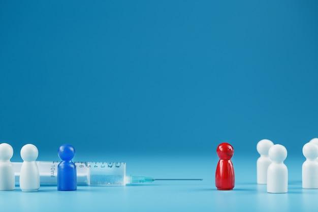 파란색 배경에 중앙에 있는 주사기의 예방 접종에 대한 빨간색과 파란색 남자의 서로 다른 의견의 모순
