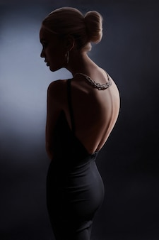 Contrast fashion woman portrait on dark wall, the silhouette of a woman with a beautiful curved back. naked back of a woman in the dark. luxury blonde posing in evening dress
