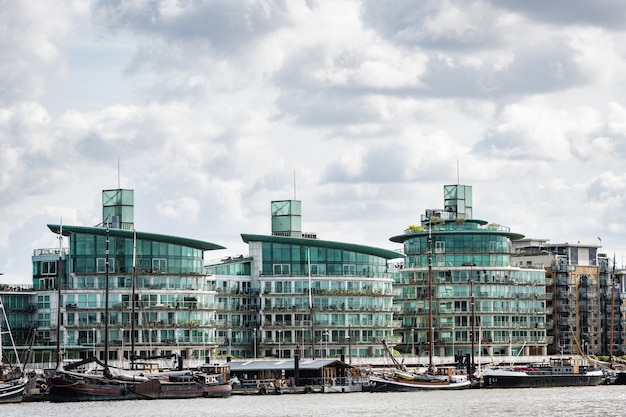 Contrast of modern glass architecture and old houseboats moored on the river thames in london, uk.