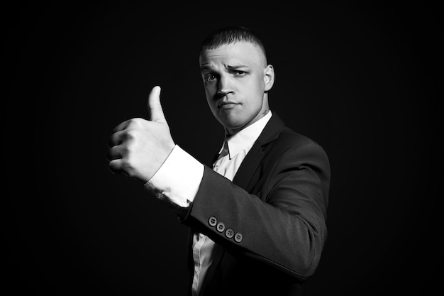 Contrast portrait of a man businessman in an expensive business suit on a dark wall. successful emotional manager businessman posing gestures with his hands on black