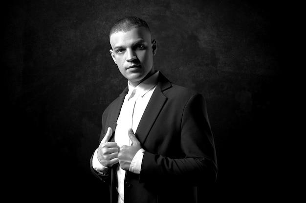어두운 배경에 비싼 비즈니스 정장을 입은 남자 사업가의 대조 초상화. 성공적인 감정적 매니저 사업가가 검은색 손으로 몸짓을 하고 있다