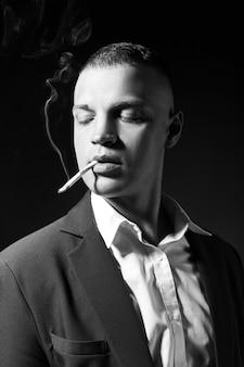 어두운 배경에 비싼 비즈니스 정장을 입은 흡연하는 남자 사업가의 대조 초상화. 성공적인 감정적 인 관리자 사업가 제스처 손 포즈와 검정에 담배 흡연