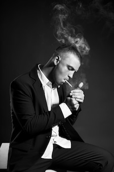 Contrast portrait of a smoking man businessman in an expensive business suit on a dark wall. successful emotional manager businessman posing gestures hands and smoking cigarette on a black