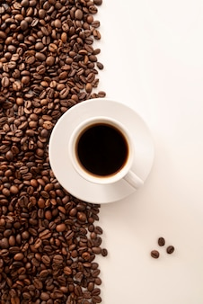 Contrasted coffee beans background and cup