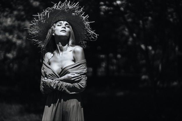 Контрастный черно-белый портрет сексуальной гламурной девушки в шляпе и платье на природе. с зернистостью пленки, шумом