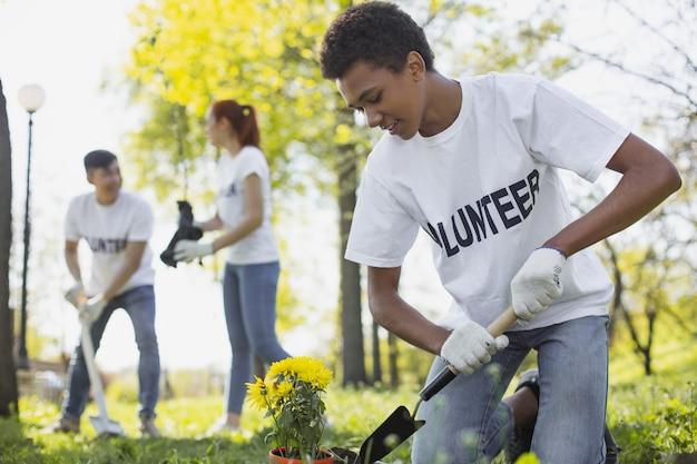 지역 사회에 대한 공헌. 정원 도구를 사용하면서 내려다 보는 매력적인 남성 자원 봉사자의 낮은 각도